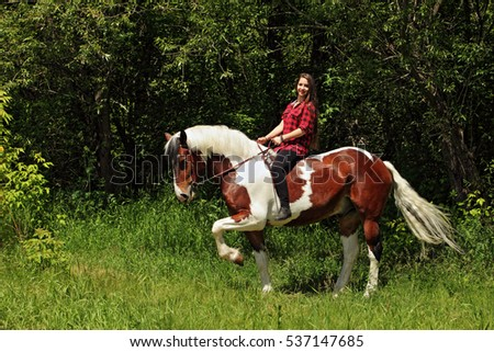 Young pretty country girl on horseback in the forest