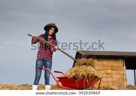 Young pretty country woman working on the farmland, loading wheelbarrow with animal manure and straw - stock photo