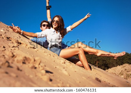 Young pretty cute couple in love having fun and laughing together on the beach in summer time.  - stock photo