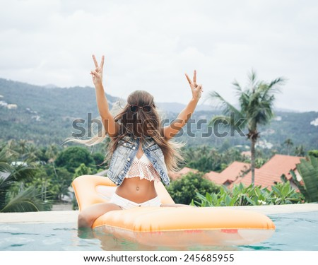 Young pretty fashion sport woman having fun outdoor in summer on tropic island in hot weather on pool party - stock photo