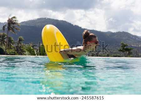 Young pretty fashion woman body posing in summer in pool with clear water lying inner tube and having fun - stock photo