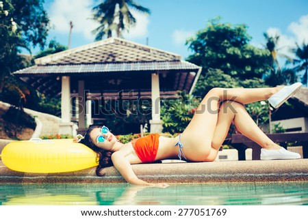 Young pretty fashion woman body posing in summer in pool with clear water lying on mattress in color bikini and having fun - stock photo