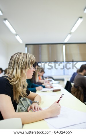 young pretty female college student sitting in a classroom full of students during class (shallow DOF; color toned image) - stock photo