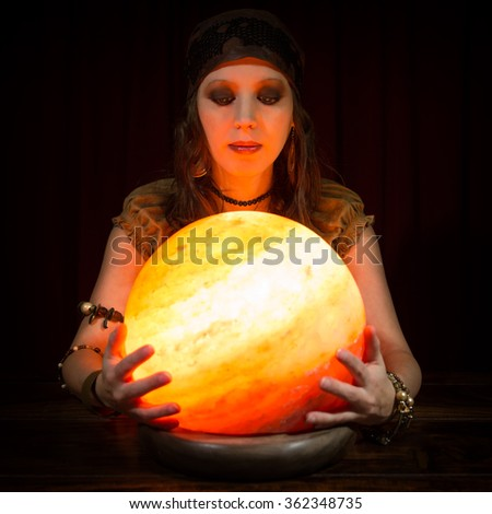Young pretty female fortune teller with a crystal ball, dark background - stock photo