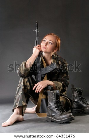 Young pretty female model in military outfit with AK-74 (Kalashnikov) assault rifle in studio - stock photo