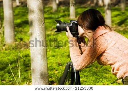 Young pretty female photographer in a forest. - stock photo