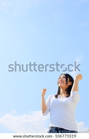 Young pretty female with arms out spread standing outdoors - stock photo