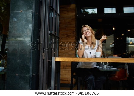 Young pretty female with good mood talking on mobile smart phone with her friend while relaxing in cafe, happy woman speaking with cell telephone while sitting in coffee shop during morning breakfast  - stock photo