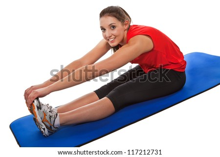 Young pretty fit woman stretching forward on blue yoga mat. Studio Isolated on white. High key. Part of a collection of this model exercising in different poses - stock photo
