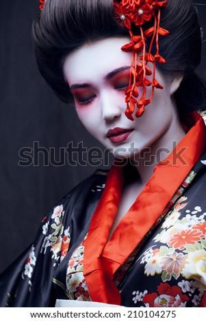 young pretty geisha in kimono with sakura and decoration - stock photo