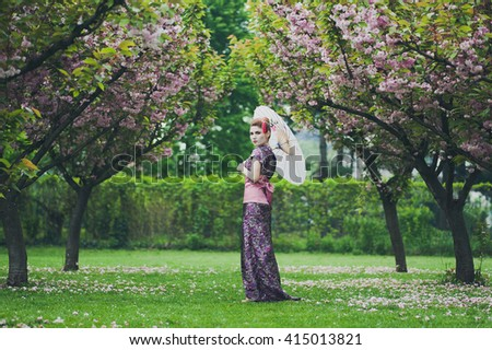 young pretty geisha walking in the garden and wearing traditional japanese kimono and traditional umbrella and cherry blossom - stock photo