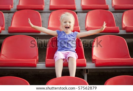 Young pretty girl cries and sitting on the audience bleachers - stock photo