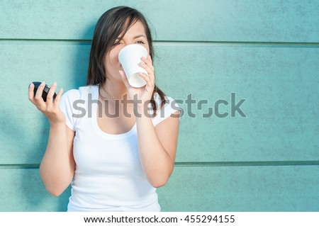 Young pretty girl drinking from takeaway coffee mug outside on green wall background with copy text space - stock photo