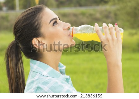 Young pretty girl drinking juice from a bottle outdoor - stock photo