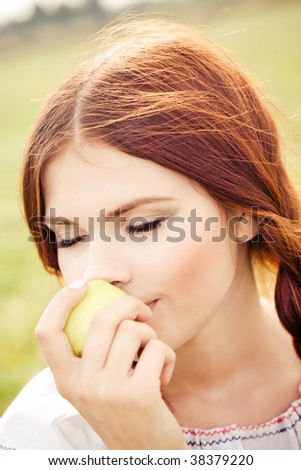 Young pretty girl eating an apple - stock photo