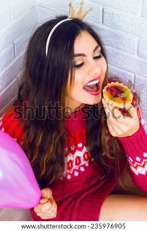Young pretty girl having fun on birthday party, wearing party crown casual sweater, holding pink balloon and tasty small fruit cake. Positive emotions, read for celebration. - stock photo