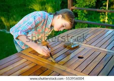 young pretty girl holding a brush applying varnish paint on a wooden garden table - Garden Furniture Varnish
