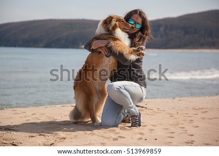 Young pretty girl hugging rough collie dog at the beach
