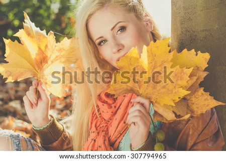 Young pretty girl in autumn park is holding yellow maple leaves is wearing mint color sweater