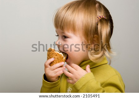 young pretty girl in green eating bred - stock photo