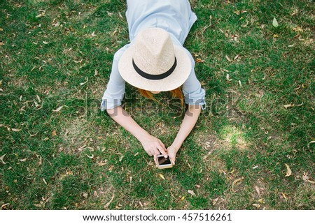 Young pretty girl in straw hat and dress lying on the grass in park  using mobile smart phone top view. Woman typing text message on smart phone using internet - stock photo