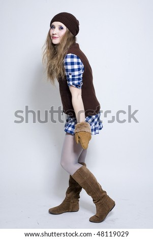 Young pretty girl in warm clothes in studio - stock photo