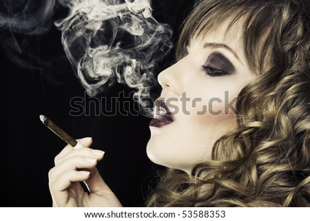 Young pretty girl is smoking cigarette - stock photo
