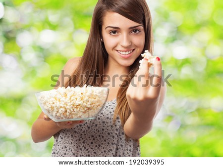 young pretty girl offering pop corn looking at the front - stock photo