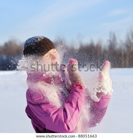 Young pretty girl playing snowball fight - stock photo