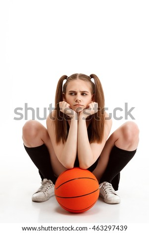 Young pretty girl posing with basketball over white background.