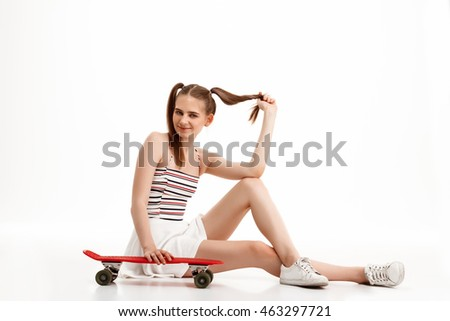 Young pretty girl posing with skateboard over white background.