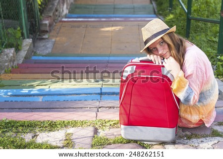 Young pretty girl sitting in the street with red suitcase. Travel concept. - stock photo