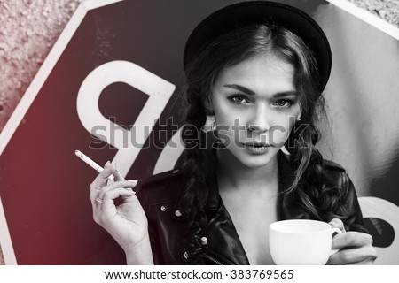 Young pretty girl sitting on the balcony smoking cigarette with cup of hot coffee espresso. Lifestyle. Stop smoking. Hipster girl in black hat with cup of coffee smoking cigar. Kiss. Swag.