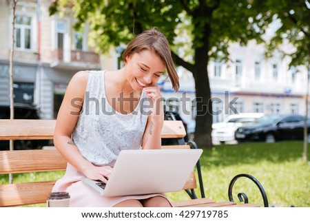 Young pretty girl sitting on the bench and laughing in the park using laptop - stock photo