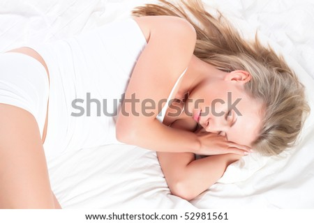 Young pretty girl sleeping in bed. Sweet dreams - stock photo