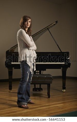 Young pretty girl standing in front of a piano in indoor concert hall - stock photo