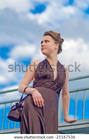 young pretty girl standing on the platform with head turned up and inclined left thinking in free pose relaxing blue skies