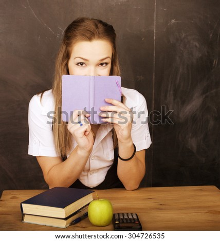 young pretty girl student in classroom at blackboard doing homework - stock photo