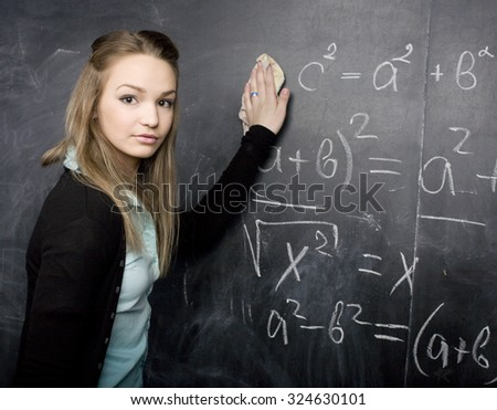 young pretty girl student in classroom at blackboard doing homework smiling - stock photo