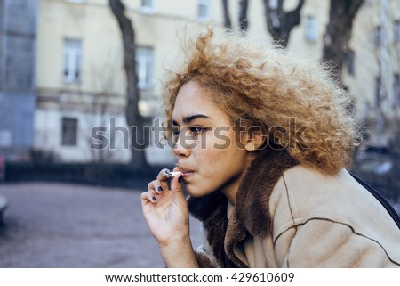 young pretty girl teenage outside smoking cigarette, looking like real junky, social issues concept - stock photo