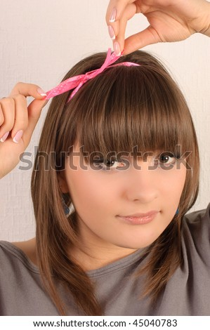 Young pretty girl, tied her hair with a ribbon - stock photo