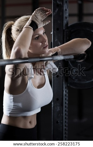 Young pretty girl tired after weightlifting at gym - stock photo