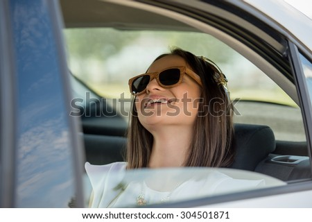 Young pretty girl wearing sunglasses listening music with headphones in car. Summer fun - stock photo