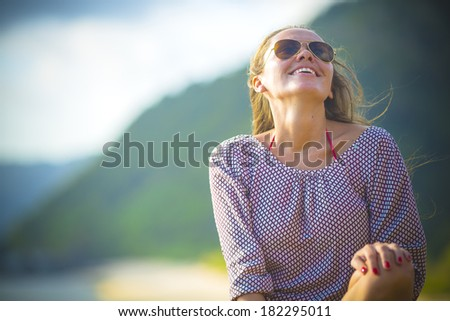 young pretty girl wearing sunglasses smiling - stock photo