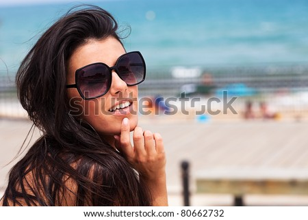 young pretty girl wearing sunglasses smiling with the beach as a background - stock photo