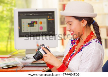 Young pretty girl wearing white shirt and fashionable hat, sitting by computer desk holding a camera, seen from profile angle