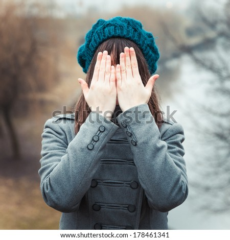 young pretty girl with hands over eyes outdoors - stock photo