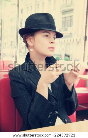 Young pretty girl with hat at the street cafe  - stock photo