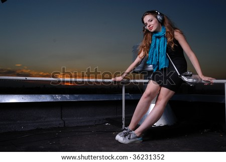 young pretty girl with headphones on the roof