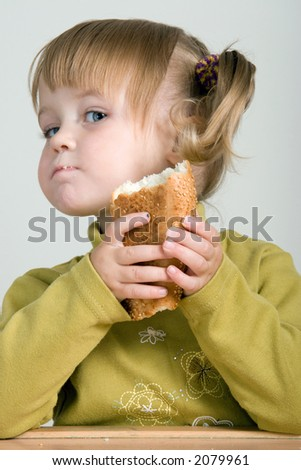 young pretty girl with ponytail eating bread - stock photo